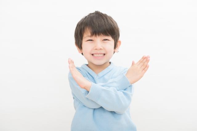 ばつを作る子供の画像